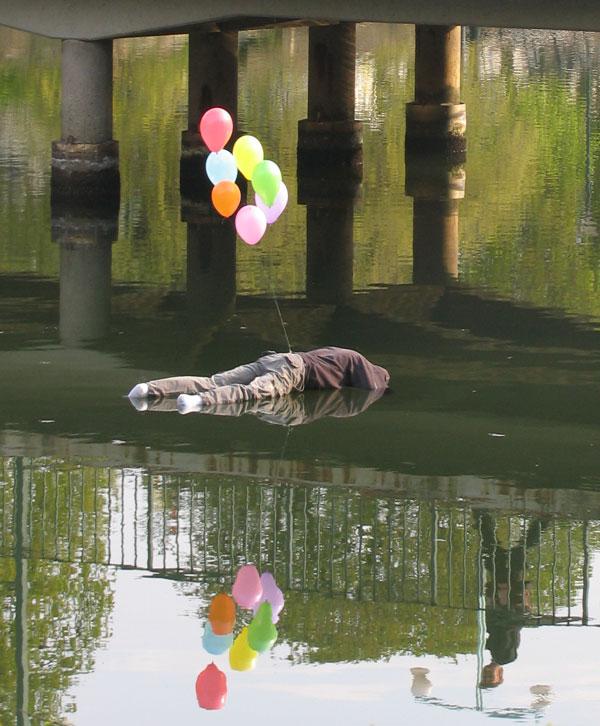 escultura real simulando que esta ahogado en un canal
