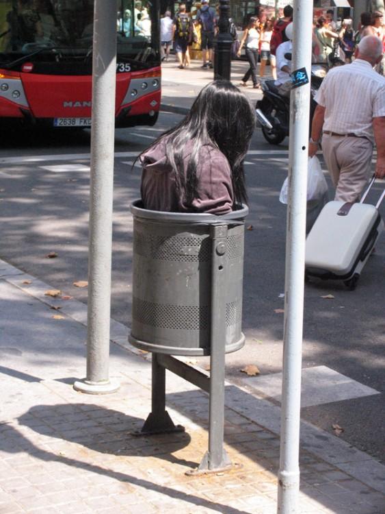 escultura real dentro de un bote de basura en la calle