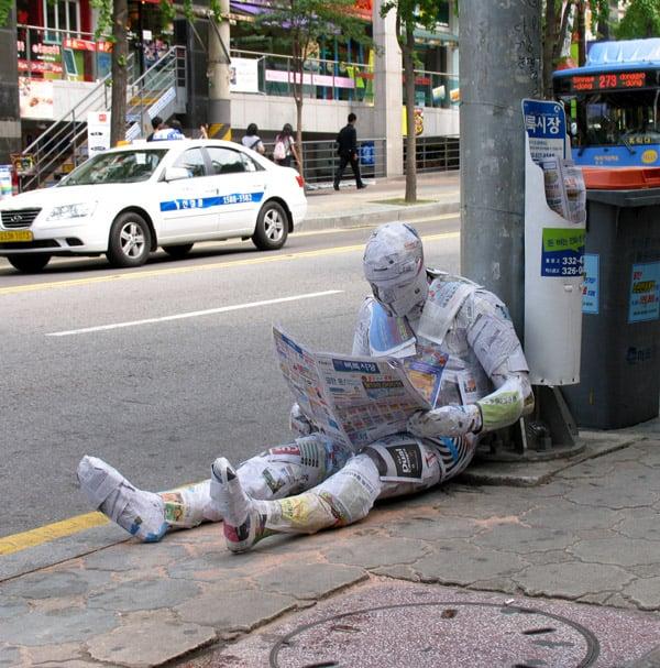 escultura envuelta de periódicos recargada sobre un poste