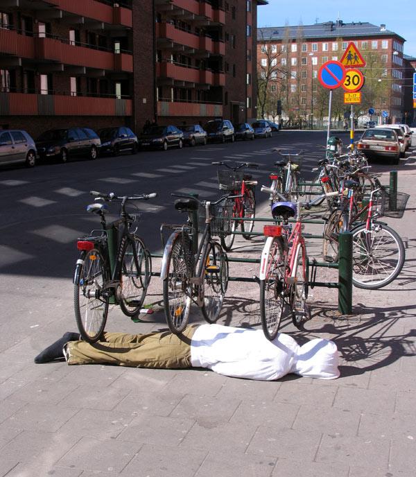 impresionante escultura del cuerpo de una persona debajo de unas bicicletas