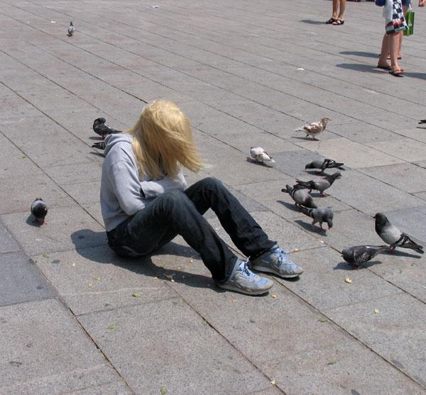 escultura real de una mujer sentada en el suelo de una plaza