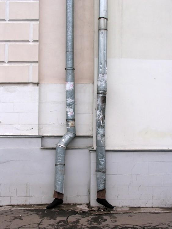 tubos sobre una pared de donde salen unos pies