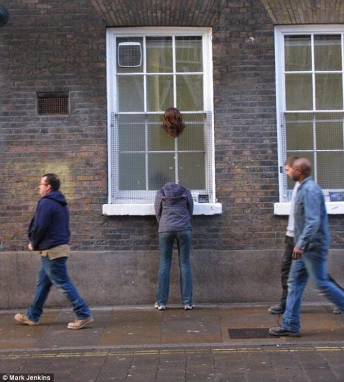 escultura de Mark Jenkins cerca de una ventana