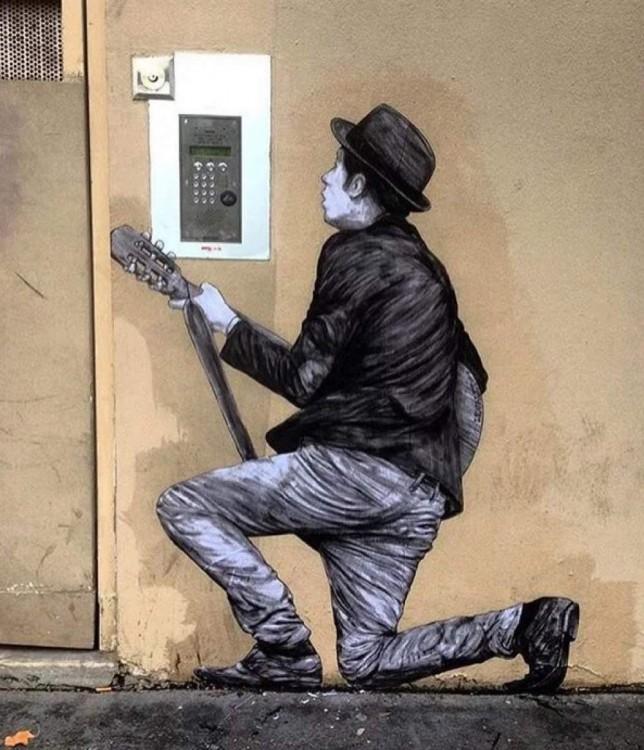 pared con el dibujo de un hombre dando serenata en París
