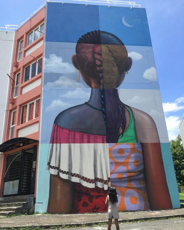 mural de un edificio con el dibujo de la parte trasera de una niña en Le Port