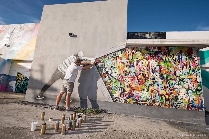 pintura de un dibujo jalando la pintura de una pared y mostrando garabatos de colores en una de las paredes de Miami