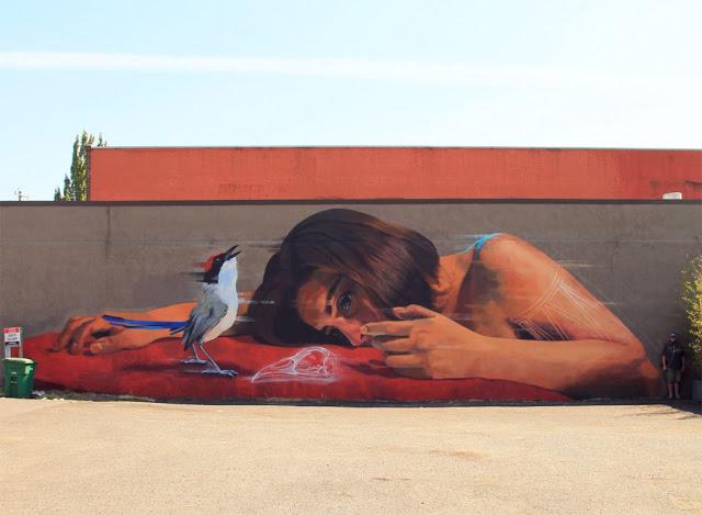 Mural de una mujer viendo un colibrí pintado en Portland, USA