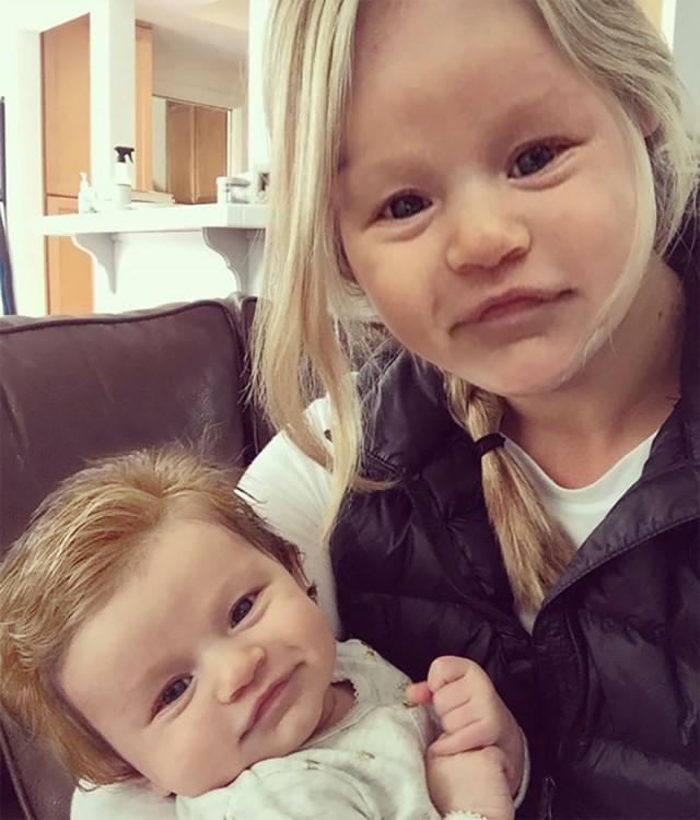 Isabelle Kaplan, la bebé con mucho cabello junto a su mamá con la cara idéntica