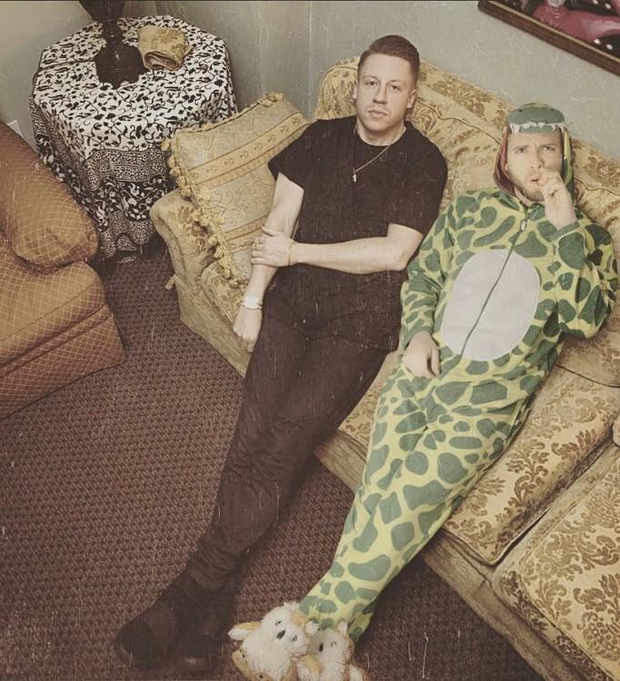 chico vestido de dinosaurio sentado en un sillón a lado de Macklemore