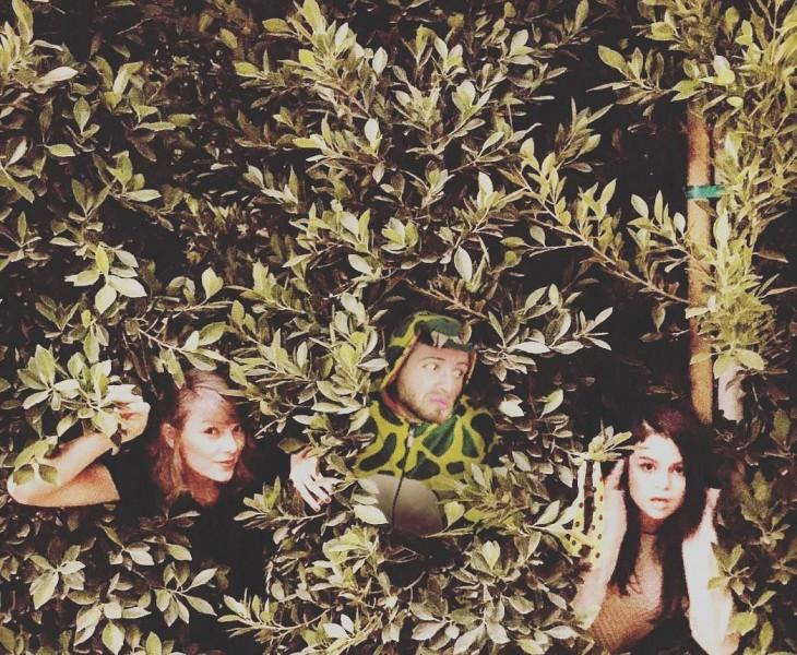 phtoshop de un chico vestido de dinosaurio escondido entre unos arbustos con Taylor Swift y Selena Gomez