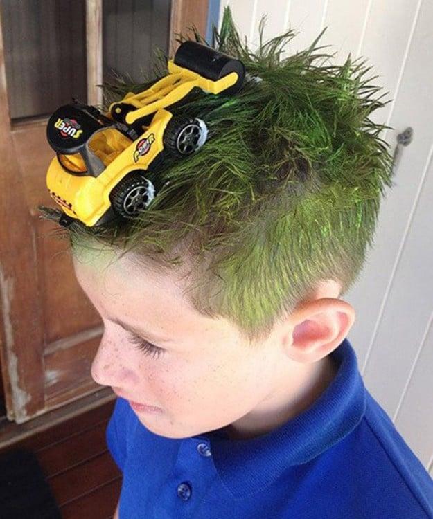 niño con el cabello verde y un tractor de juguete encima de él