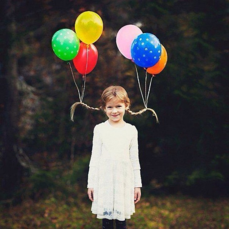 niña con dos trenzas y globos atados a ellas