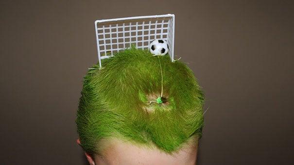 cabeza de un niño con el cabello de color verde y una portería de fútbol