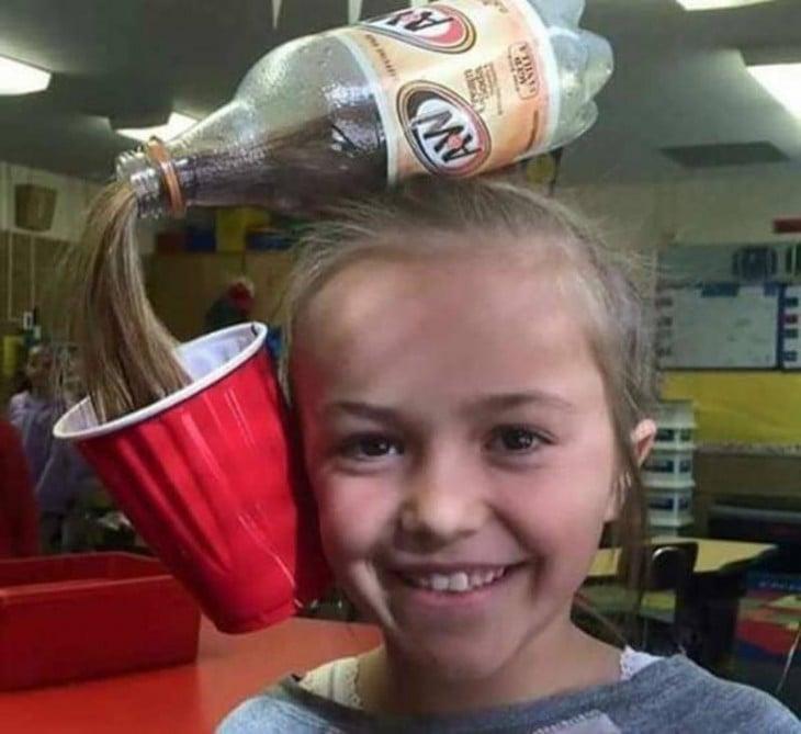peinado de una niña simulando ser un refresco vaciándose sobre un vaso rojo
