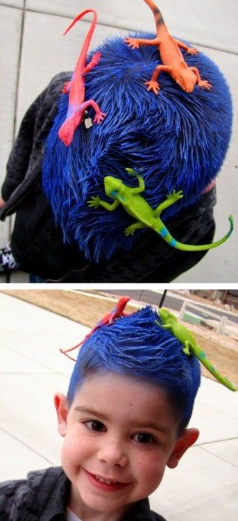 niño con el cabello de color azul y unas iguanas de juguete encima