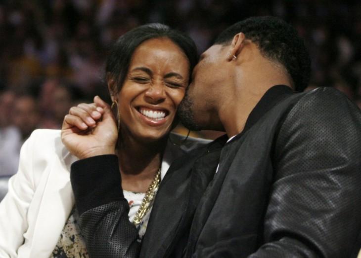will smith dando un beso a su esposa mientras ella sonríe