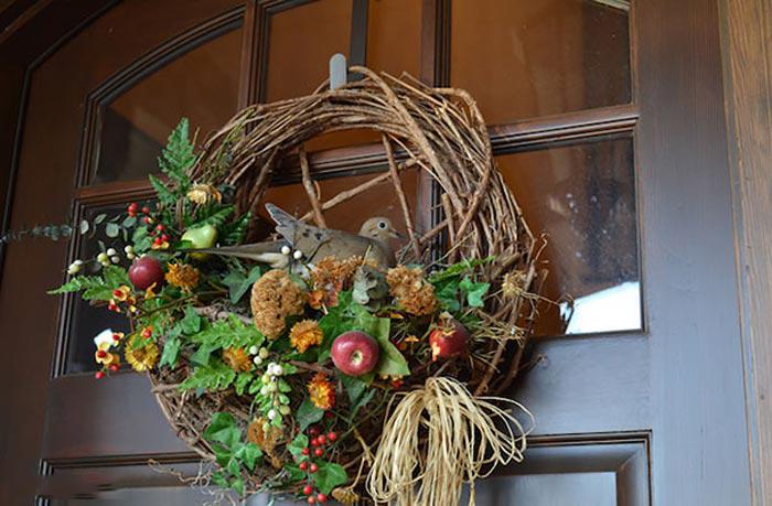 Nido de ave sobre el adorno de la puerta de una casa