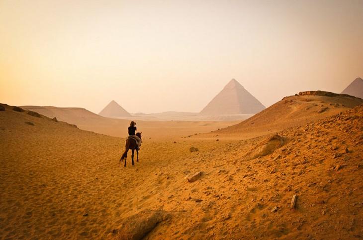 mujer en desierto admirando las piramides en Egipto