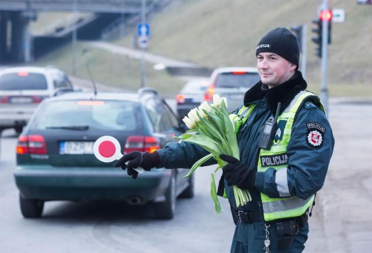 Oficial de Lituania parando el tráfico con flores en la mano