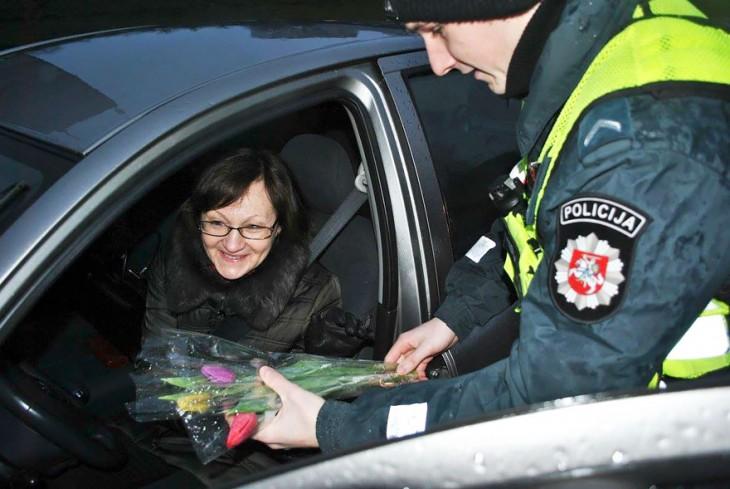 Policía regalando flores a una mujer en Lituania, Europa