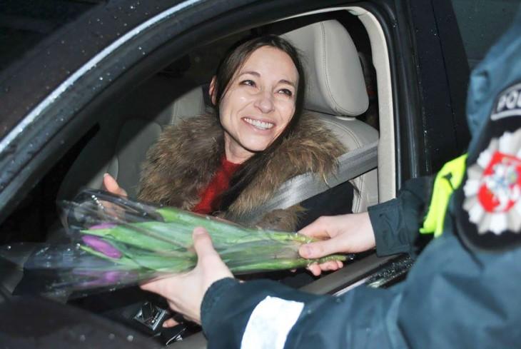 mujer feliz recibiendo flores por parte de la policía de Lituania