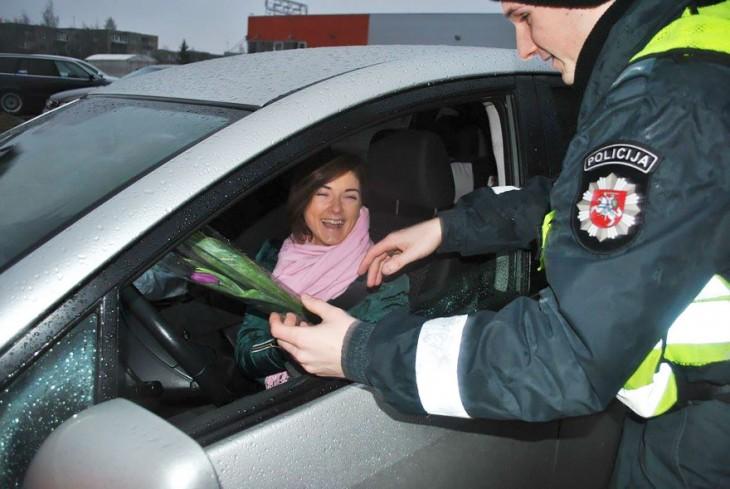 Mujer sonriendo mientras recibe flores de un policía en Lituania