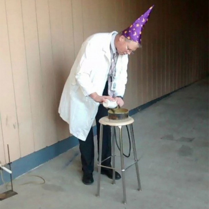 profesor de física durante un experimento usando un gorro de mago