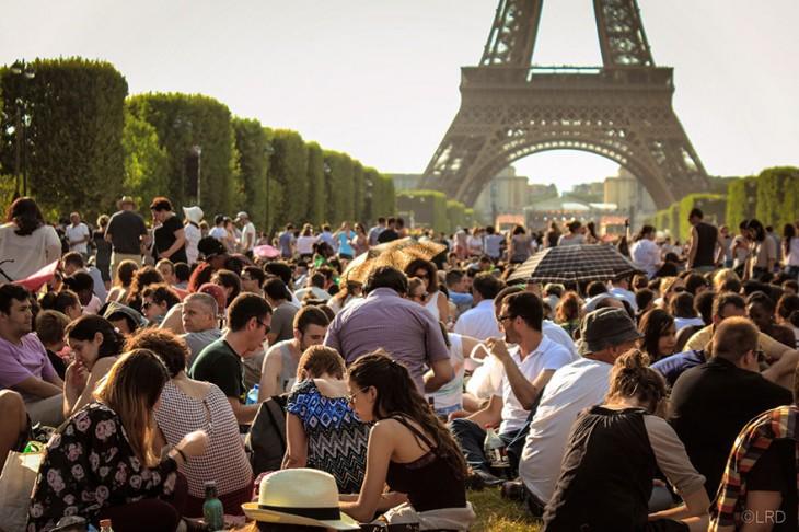 miles de personas sentadas frente a la torre eiffel