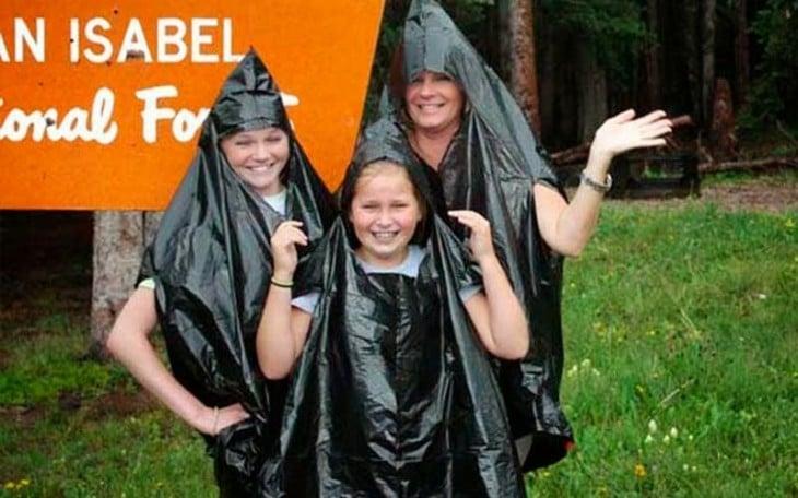 meninas com sacos de lixo pretos como capas de chuva