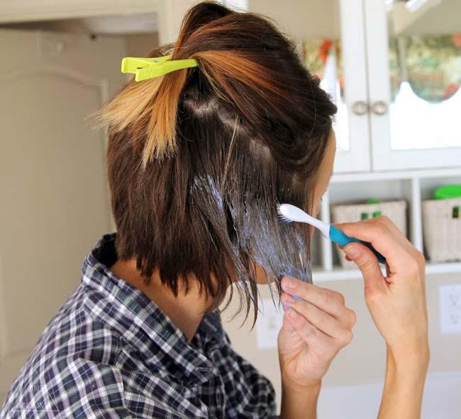 mujer pintando su cabello con un cepillo dental
