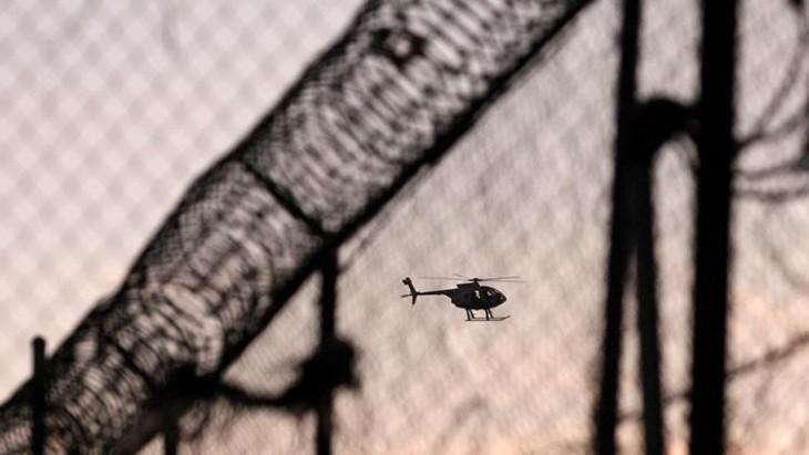 Helicóptero volando sobre el techo de una prisión