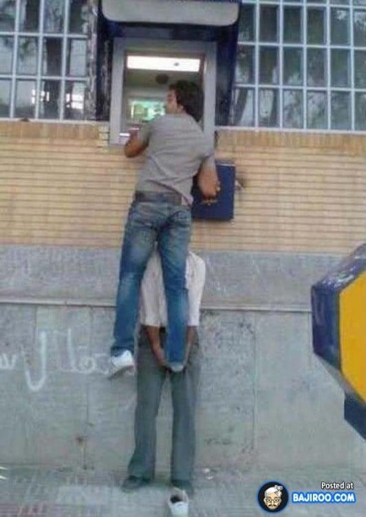 Persona cargando a otra para retirar dinero de un cajero muy alto