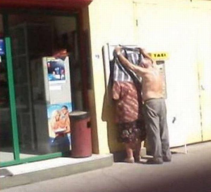 hombre se quita su camisa para evitar que alguien vea la pantalla del cajero