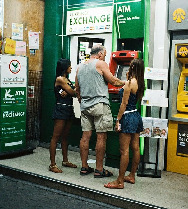 hombre en Tailandia retirando dinero de cajero junto a dos jóvenes mujeres a su lado