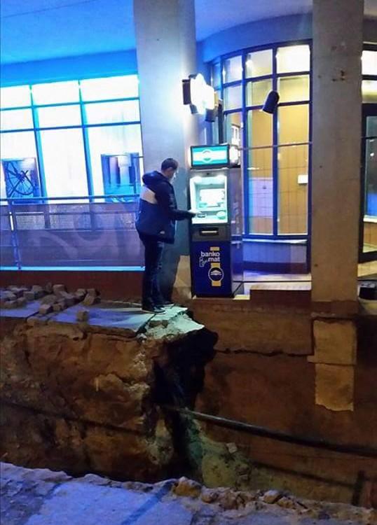 Hombre al borde de banqueta en reconstrucción usando un ATM