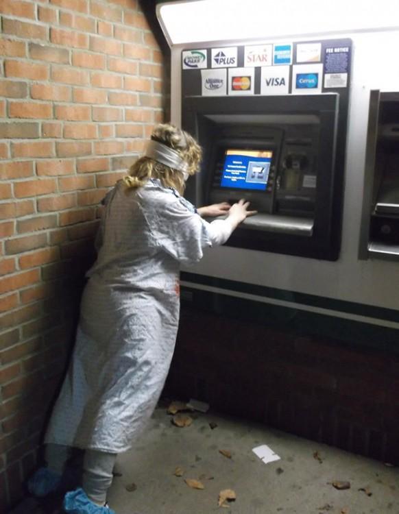 Mujer con bata de hospital y ojos vendados queriendo usar el ATM