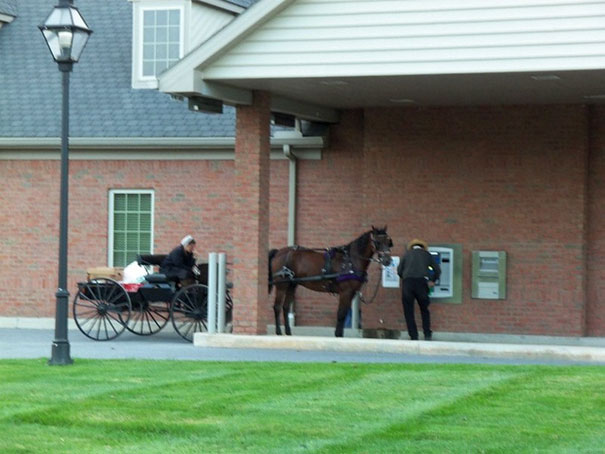 Hombre con caballo y carreta usando el cajero automático