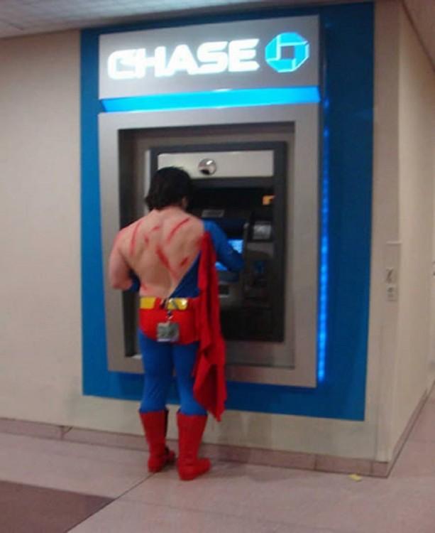 Spiderman con el traje rasgado retirando efectivo