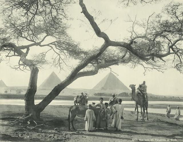 grupo de lugareños y piramides al fondo