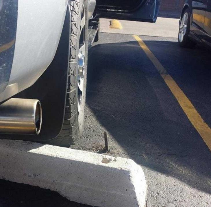 Un tornillo en el cemento del cajón para estacionarse