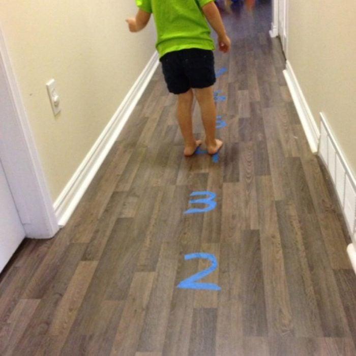 niña saltando en el suelo con números hechos de cinta adhesiva
