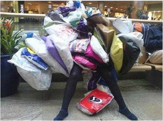mujer con muchisimas bolsas de compras encima