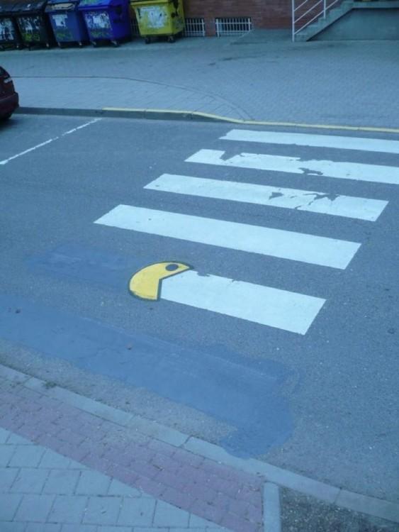 dibujo de pacman simulando que se come un señalamiento en el pavimento de una calle