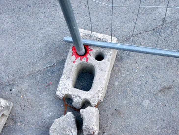tubo perforando un ladrillo con un poco de pintura roja