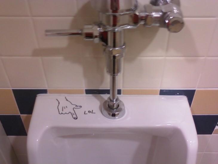 urinal con una mano señalando hacia abajo con la palabra Lol