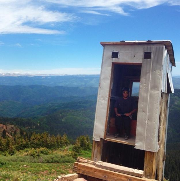 hombre sentado en un baño sobre la montaña en Colorado