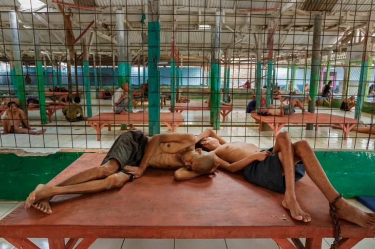 dos personas acostadas en una jaula de un hospital en Indonesia