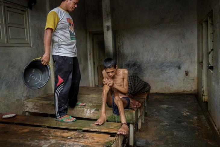 persona bañando a un paciente en un hospital mental de Indonesia