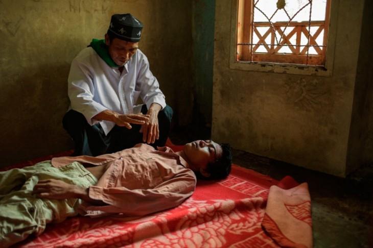 persona haciendo curación a un paciente de un hospital mental en Indonesia