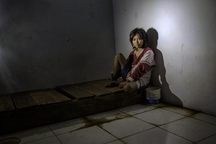 Fotografía de una chica sentada en una base de madera recargada en la pared en un hospital mental en Indonesia